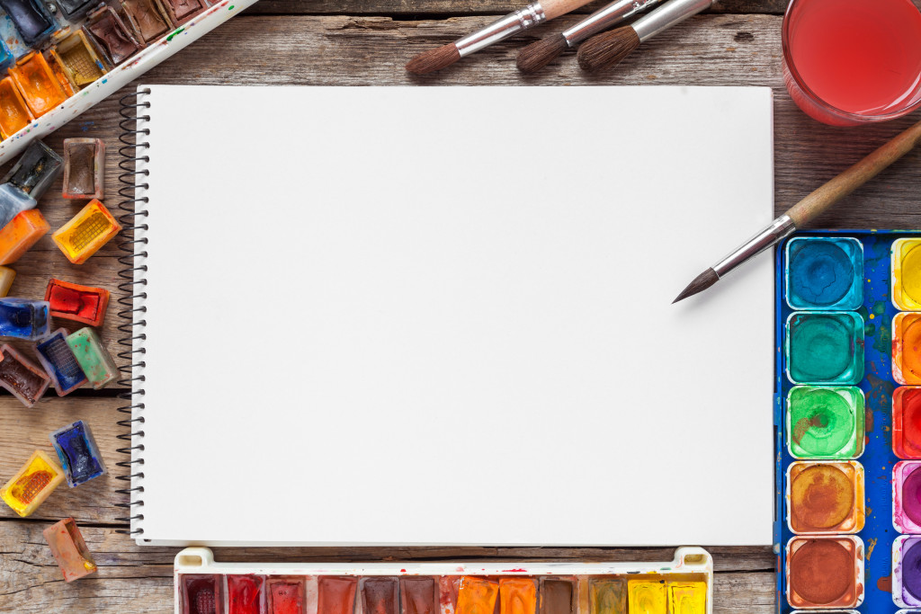 Set of watercolor paints brushes for painting and blank white paper sheet of sketchbook on vintage wooden background. Top view.