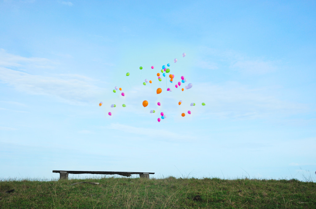 Empty wooden bench with colorful balloons flying away to the blue sky background